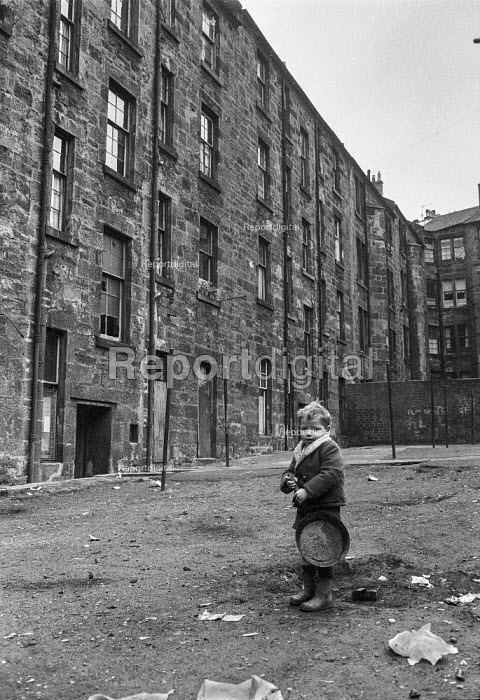 Boy playing with rusty frying pan in courtyard, Glasgow tenement 1971 - Martin Mayer - 1971-06-23