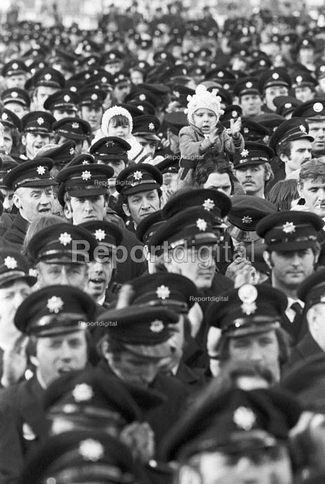 Firemens pay strike 1977. Mass meeting in Hyde Park after a march through London. Fireman and child - Peter Arkell - 1977-11-26