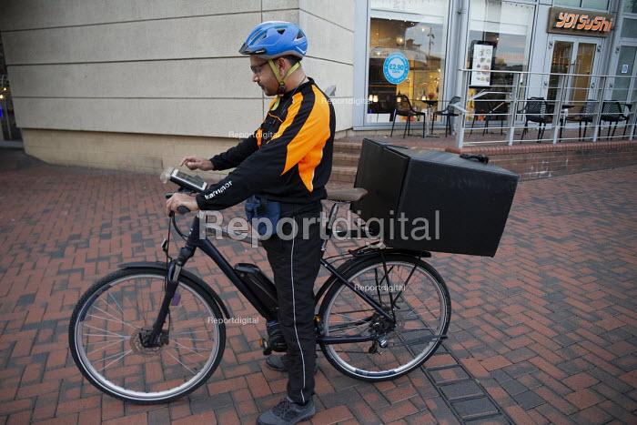 Ubereats delivery rider checking his App, Shopping Centre, Reading, Berkshire - John Harris - 2018-10-13