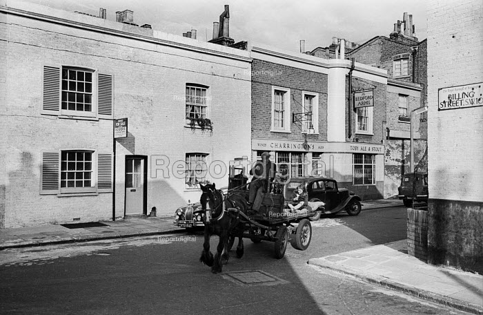 Rag 'n' Bone Man riding a horse and cart through Chelsea streets 1958 with little girl on the back of the cart eating an ice cream - Alan Vines - 1958-07-02