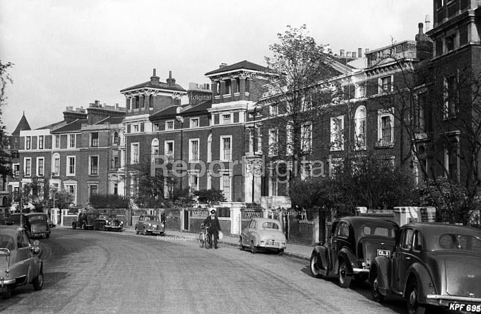 Workman walking along Gloucester Crescent, Camden, London 1958. Street with very few cars parked - Alan Vines - 1959-09-02