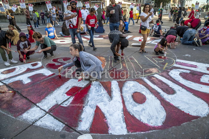 Oakland, California, USA- Hotel workers strike against low pay at the Marriott City Center Hotel sit down blocking the road, children painting the strike slogan, One Job Should be Enough, on the road outside the hotel. Members of Unite Here strike against low wages that force many workers to work an additional job besides their job at the hotel - David Bacon - 2018-10-20
