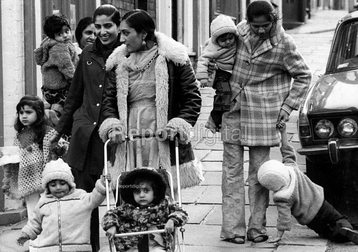 Asian mothers walking with their young children along street, Leicester 1977 - John Sturrock - 1977-11-02