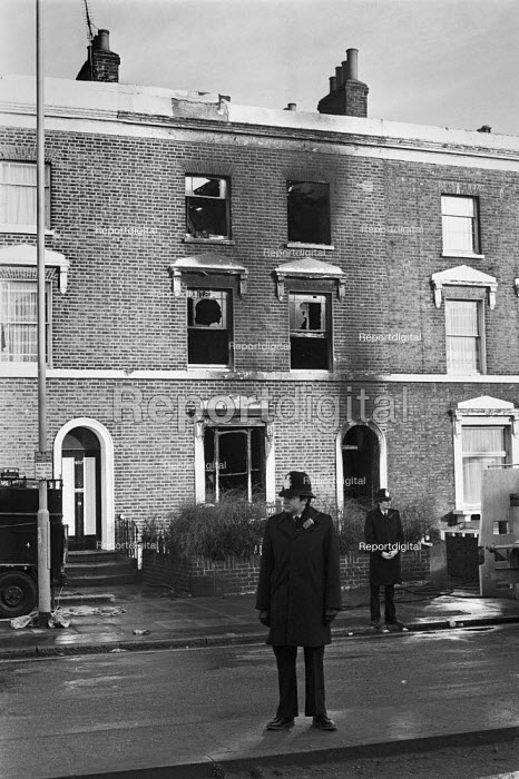 New Cross fire, where 13 young people died Deptford London 1981. The blaze broke out inside the house, either accidentally or deliberately, during a birthday party at the house, Police guarding the burnt out building - Peter Arkell - 1981-01-18