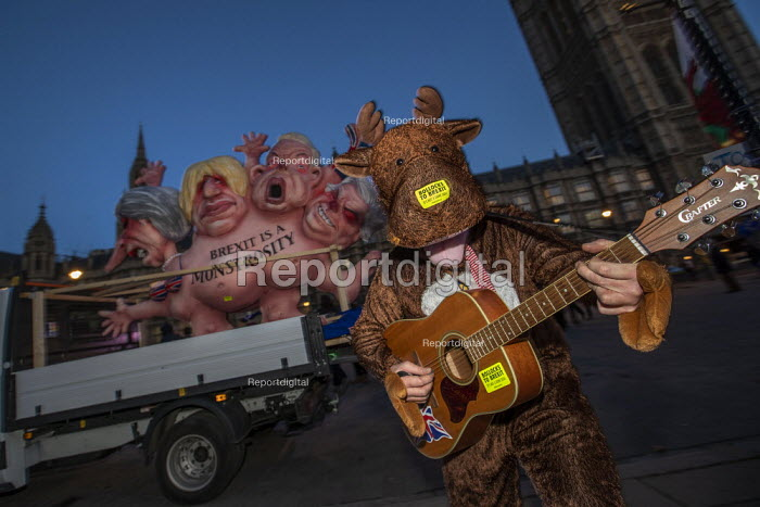 """Rudolph the reindeer with Brexit is a Monstrosity sculpture by Jacques Tilly outside Parliament on the evening of Teresa May confidence vote, Westminster, London. The float has a multi-headed chimera with the faces of Theresa May and three leading Brexit campaigners: Boris Johnson, Michael Gove and David Davis with the inscription """"Brexit is a monstrosity"""" - """"Let's stop it"""" - Jess Hurd - 2018-12-12"""