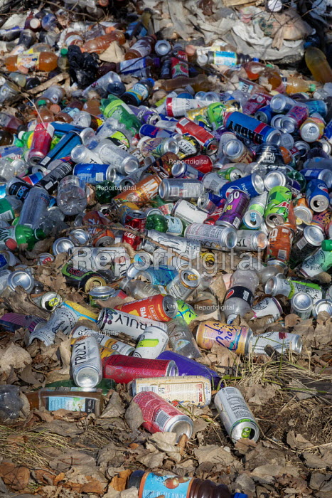 Detroit, Michigan, USA Plastic bottles and cans illegally dumped in a woods. Many are juice or water containers, which are not covered under Michigan law requiring a 10 cent deposit - Jim West - 2018-12-18