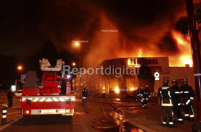 Shops burning,urban riot after two teenagers were electrocuted whilst being chased by police at Clichy sous Bois. Firefighters, the Mondial Moquette store burning down - Sebastien ORTOLA