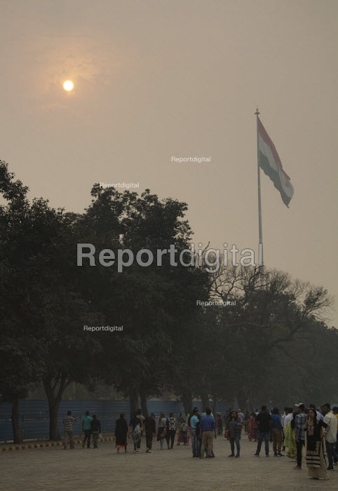 Air pollution in India. Sun shining through smog at Pakistan border. Crowds gather below Indian flag before the daily flag ceremony. Air pollution in India is a serious issue with the major sources being fuelwood and biomass burning, fuel adulteration, vehicle emission and traffic congestion - Martin Mayer - 2018-11-01