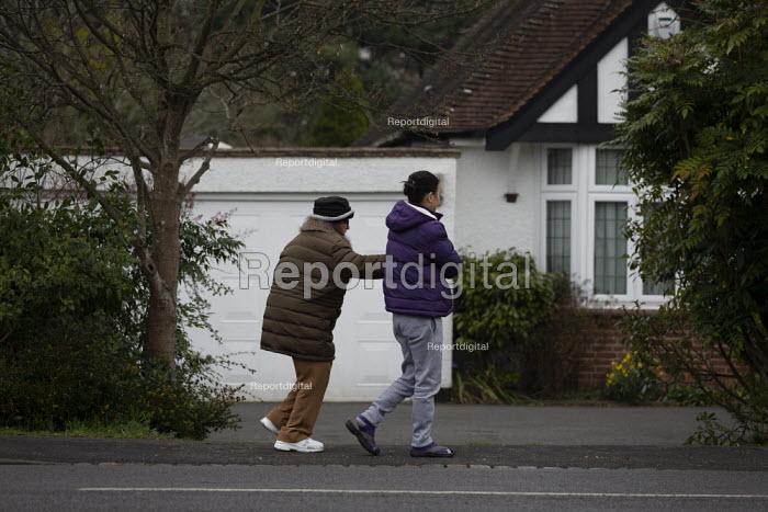Carer helping an elderly woman to walk, Stratford upon Avon, Warwickshire - John Harris - 2019-01-10