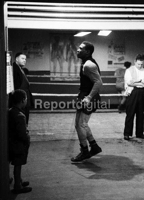 Nigerian boxer Dick Tiger in training at the gym Liverpool 1958 watched by an older man and a young boy. A professional boxer he held the World Middleweight and World Light Heavyweight Championship - Alan Vines - 1958-10-13