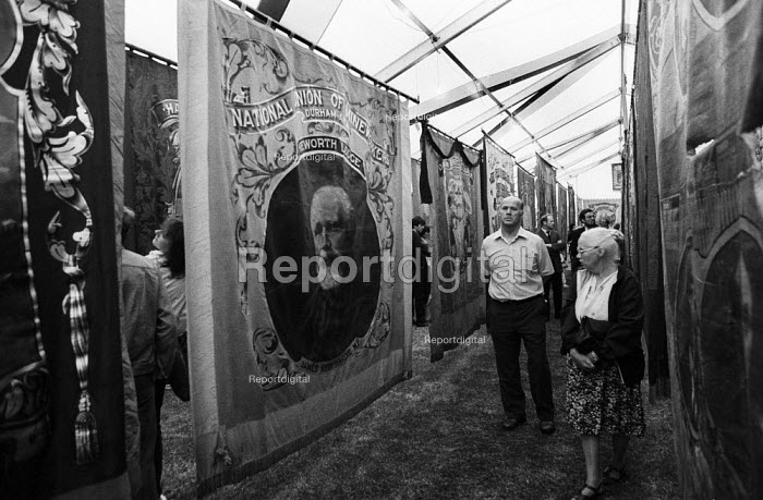 Durham MIners Gala 1986. MIners and their families admiring the Lodge banners from the Durham coalfields on display at the traditional Labour movement event with one of the founders of the British Labour Party Keir Hardie featured on the Heworth Lodge banner - Stefano Cagnoni - 1986-07-12