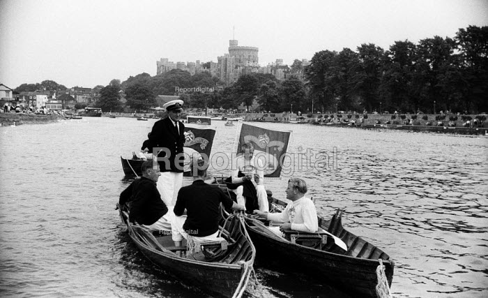 Royal Swan Upping 1959. Dating back to the 12th Century an annual census of the swan population by the Queen's swan uppers on a particular stretch of the River Thames to check the health of and count the number of swans and young cygnets and ensure that the swan population is maintained. Vintner livery company swan uppers on the River Thames with Windsor Castle behind them - Alan Vines - 1959-07-20