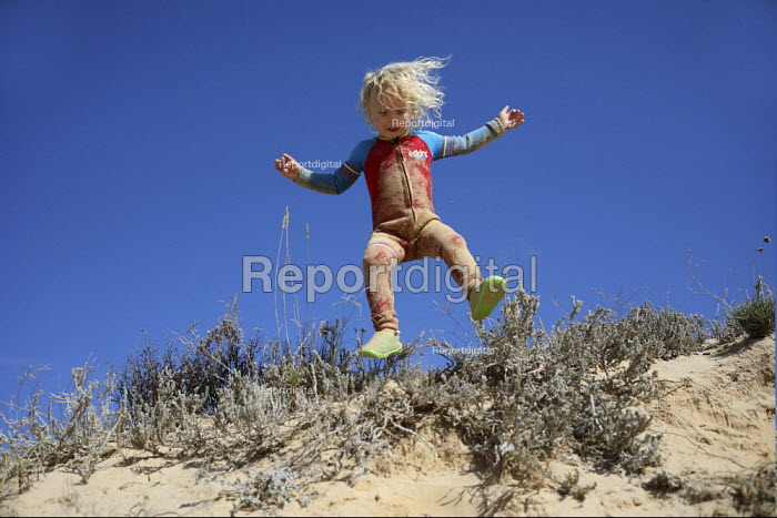 Boy playing in the sand dunes, family holiday, Amoreira, Algarve, Portugal - Paul Box - 2018-10-29