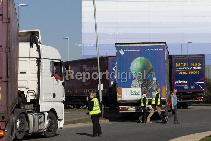 Worker directing lorries waiting to enter B&Q RCC distribution centre, Swindon - John Harris - 2019-02-25