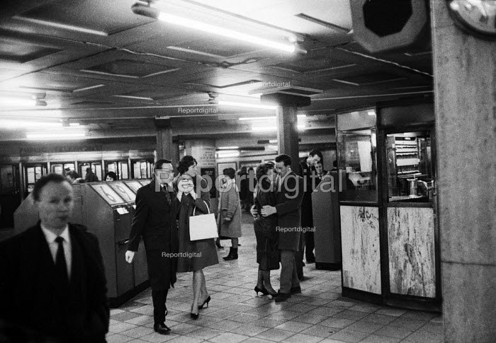 Man and woman hugging by ticket machines, Piccadilly Circus London Underground 1961 - Romano Cagnoni - 1961-02-06