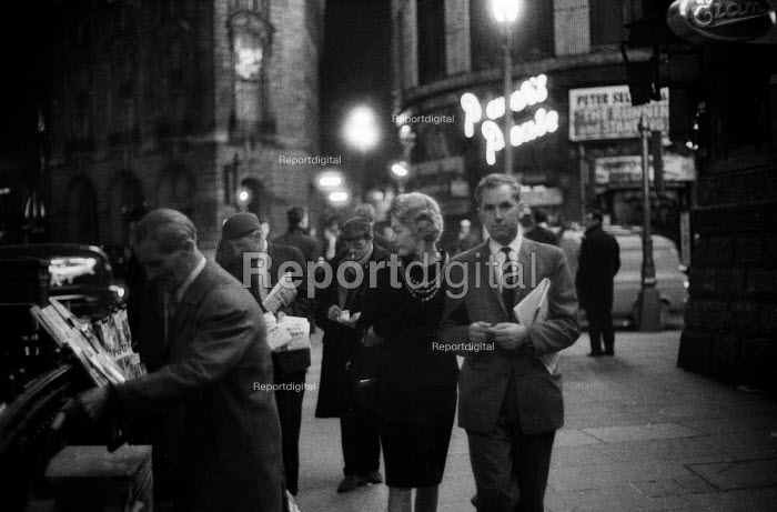 Smartly dressed couple passing newspaper seller in late... - Romano Cagnoni, RARC6179.jpg