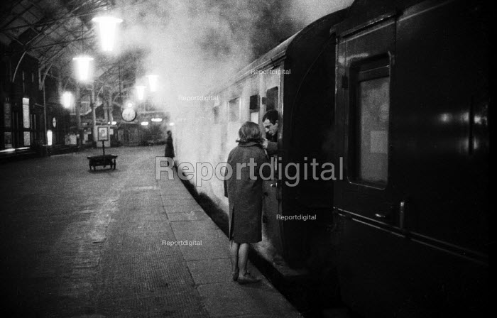 Couple saying goodbye Kings Cross Station London 1961 as late night steam train prepares to leave - Romano Cagnoni - 1961-09-13