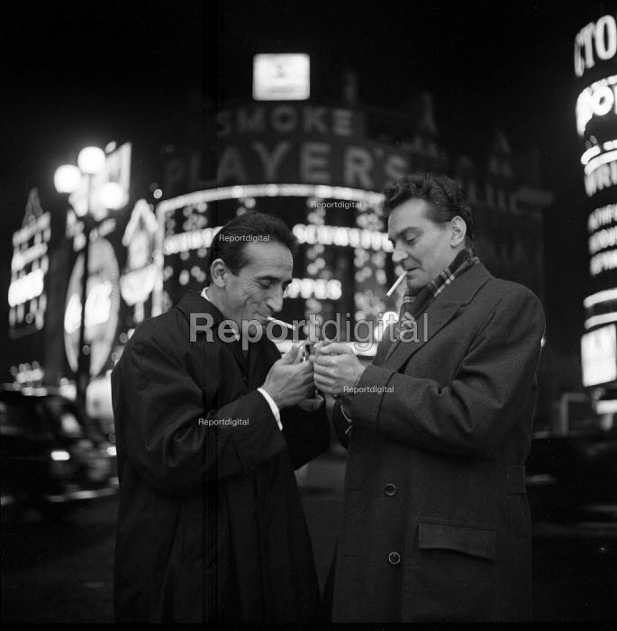 Two men smoking outside at night Piccadilly Circus London 1961 - Romano Cagnoni - 1961-09-08