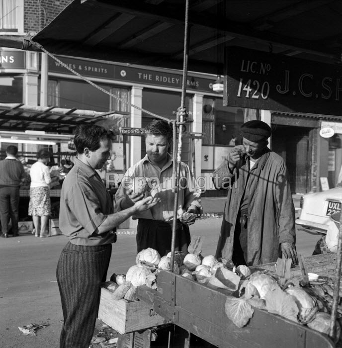 Playwright Arnold Wesker with street traders on a fruit and vegetable stall, Ridley Road Market north London 1962 - Romano Cagnoni - 1962-08-11