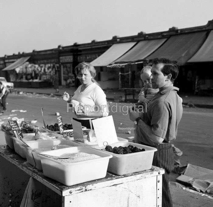 Playwright Arnold Wesker with his wife Doreen and their child at a fruit and vegetable stall, Ridley Road Market north London 1962 - Romano Cagnoni - 1962-08-11