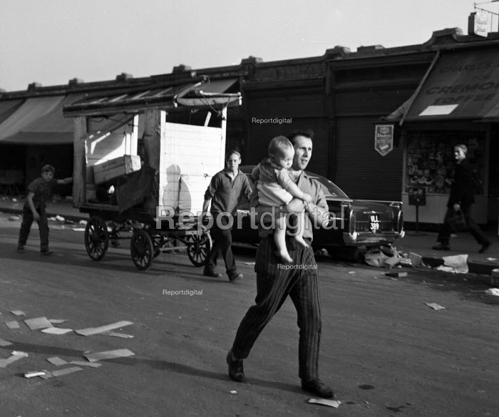 Playwright Arnold Wesker walking with his baby son Ridley Road Market north London 1962 - Romano Cagnoni - 1962-08-11