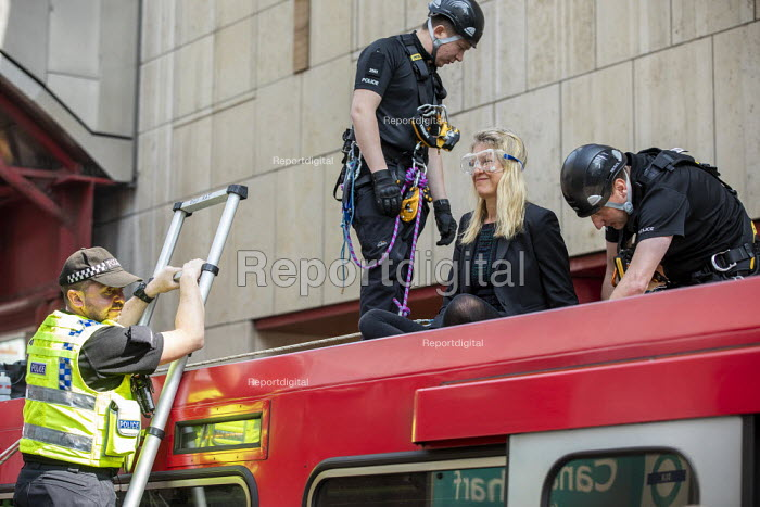 Extinction Rebellion stop DLR trains at Canary Wharf, against lack of government action on climate change. Nonviolent direct action blocking London. Police removing protestor glued onto the roof of a train - Jess Hurd - 2019-04-17