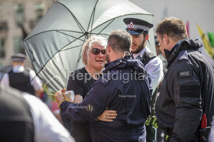 Woman hugs a police officer after being released from a lock-on during eviction of Extinction Rebellion climate change campaigners, occupation of Oxford Circus, London. - Jess Hurd - 2019-04-19