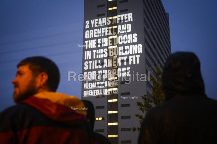 Projection of a message about tower block fire safety by Grenfell United onto Cruddas Park Tower, Newcastle Upon Tyne. 2 Years After Grenfell And The Fire Doors in this Building Still Aren't Fit For Purpose. One of three simultaneous guerrilla projections onto unsafe tower blocks around the country by the group of bereaved families and survivors of the Grenfell Tower Fire - Mark Pinder - 2019-06-12