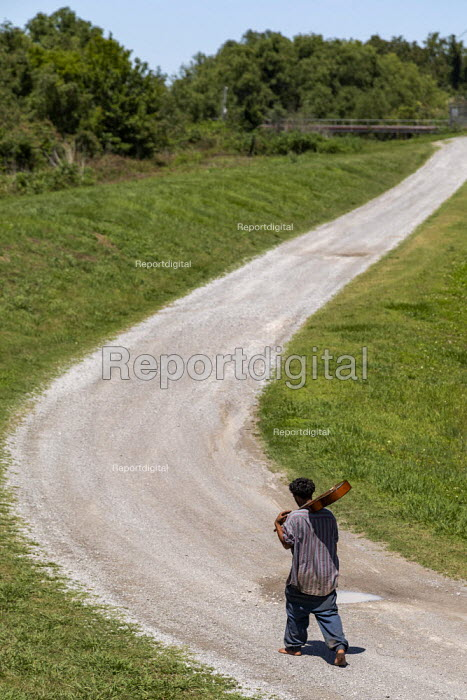 Buras, Louisiana, USA, Barefoot black man carrying a guitar on his shoulder walking along a rural road - Jim West - 2019-05-13