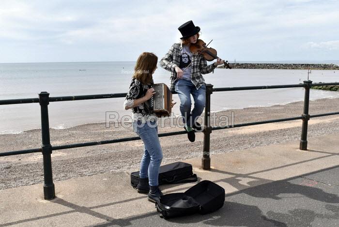 Sidmouth Folk Week. An annual gathering in Sidmouth since 1955 of British folk music and dance groups who perform their song and dance routines in the bars and on the streets of the small seaside town in Devon during a week long festival that attracts a total crowd of around sixty thousand people. Two young people busking on the Esplanade along the seafront. - Stefano Cagnoni - 2018-08-08