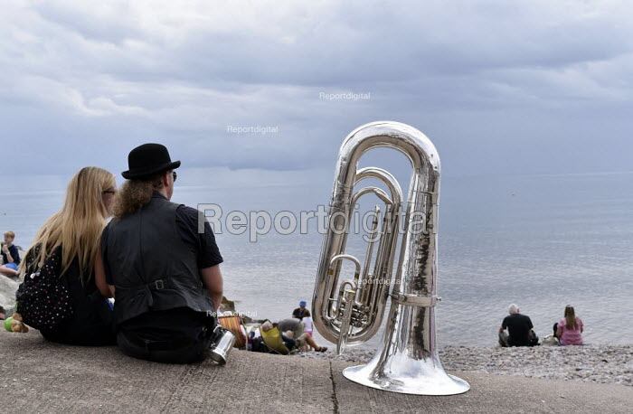 Sidmouth Folk Week. An annual gathering in Sidmouth since 1955 of British folk music and dance groups who perform their song and dance routines in the bars and on the streets of the small seaside town in Devon during a week long festival that attracts a total crowd of around sixty thousand people. Musician taking a break to relax with a friend and his tuba seated on the Esplanade by the sea. - Stefano Cagnoni - 2018-08-08