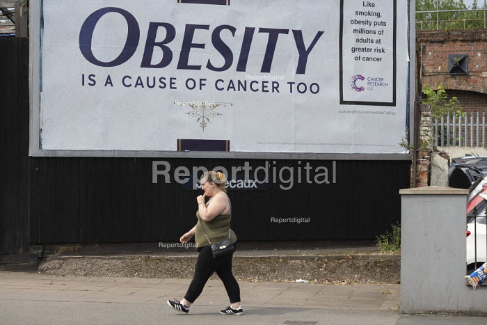 Obesity is a cause of cancer too advertisement Cancer Research UK obesity campaign, which highlights excess weight as a cause of cancer. The billboard looks like a cigarette packet. Some members of the public have accused Cancer Research of spreading a Fat Shaming message - John Harris - 2019-07-16