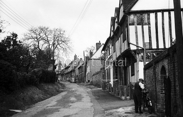 Elderly man parking his bicycle outside his home, mediaeval village of Lavenham Suffolk 1958 - Kurt Hutton - 1958-10-20
