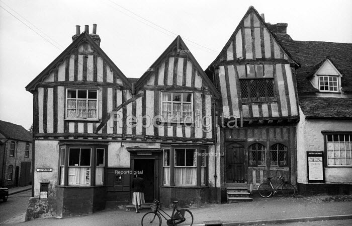 Woman walking into the Post Office on the High Street in the mediaeval village of Lavenham Suffolk 1958. The Crooked House - Kurt Hutton - 1958-10-20