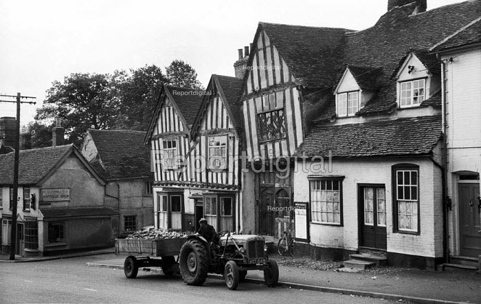 Farmhand with tractor and produce passing The Crooked House in the mediaeval village of Lavenham Suffolk 1958 - Kurt Hutton - 1958-10-20
