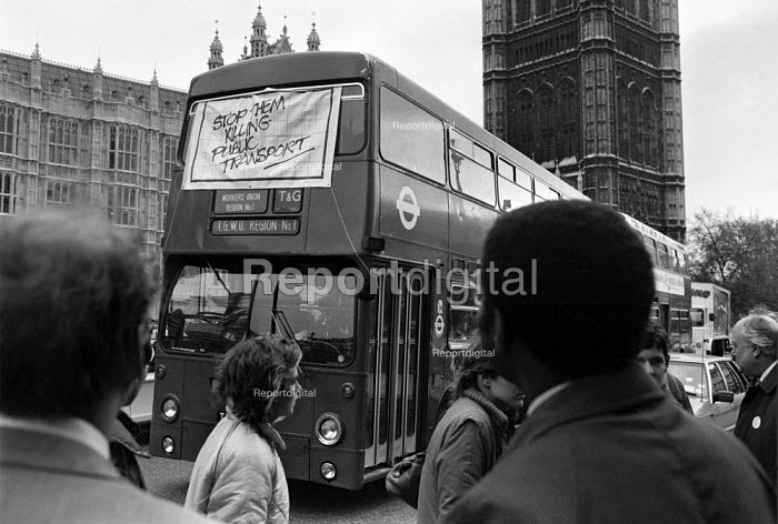 Busmen lobby Parliament against cuts, rationalisation and plans for privatisation of public transport, London 1985. Here Bill Morris (TGWU) and Norman Willis (TUC) looking at a bus with a banner Stop Killing Public Transport - NLA - 1985-04-02