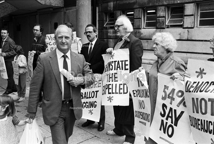 Gordon McLennan, gen sec of the Communist Party, 1985 walking past protest from his own party calling for more democracy outside a conference of the party in Hammersmith, West London. The party was in the process of a split - Peter Arkell - 1985-05-19