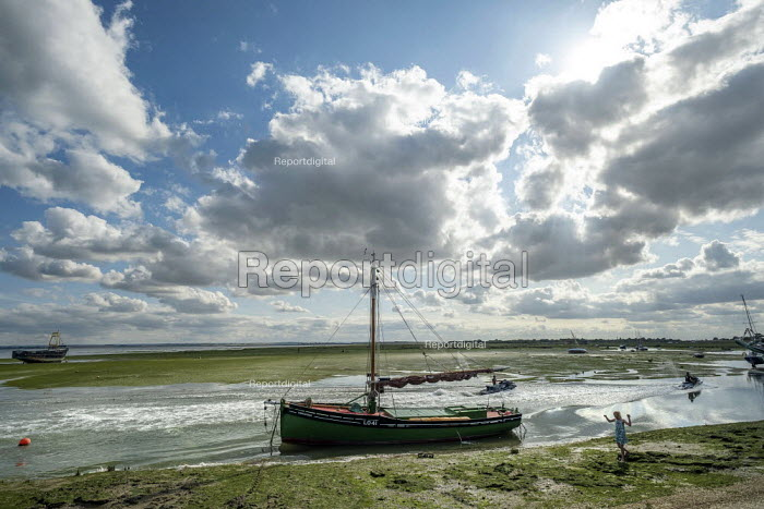 The Endeavour LO41, the first cockle boat to be fitted with an engine and one of the Little Ships that rescued troops from Dunkirk in WW2, Old Leigh, Leigh-on-Sea, Essex. Jet skis passing - Jess Hurd - 2019-08-08