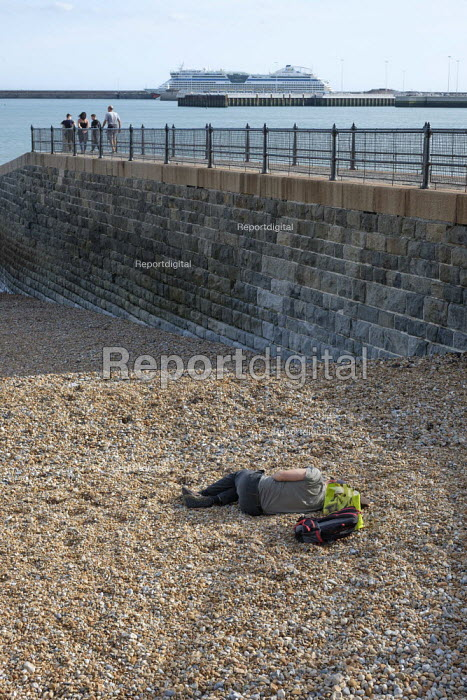 Young man sleeping on a pebble beach, luxury cruise liner, Western Harbour, Dover, Kent - Philip Wolmuth - 2019-08-15