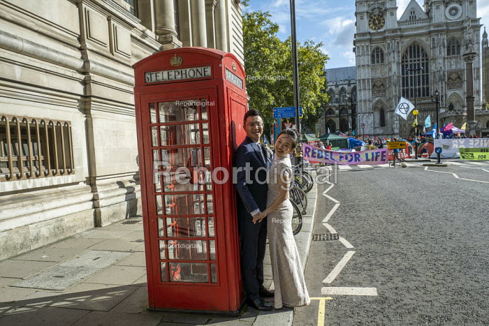 Bride and groom pose for wedding photos as Extinction Rebellion protest against lack of Government action on climate change. Nonviolent direct action shutting down central London. - Jess Hurd - 2019-10-09