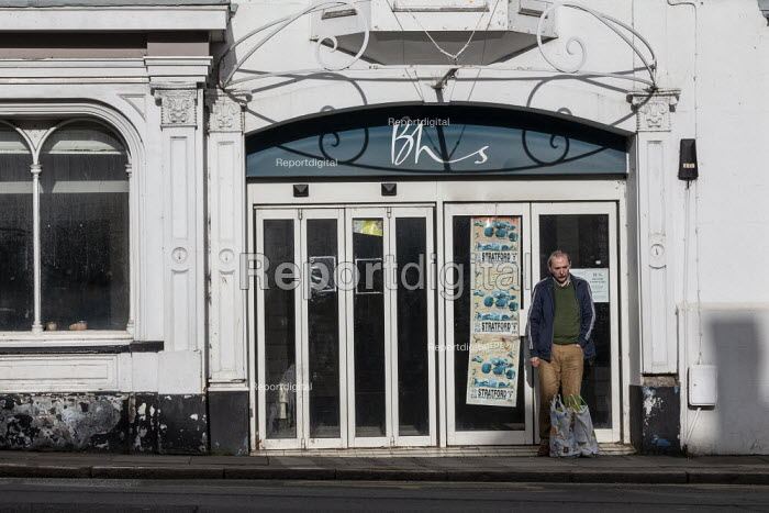 Shopper in the doorway of closed BHS Store, Stratford upon Avon, Warwickshire. British Home Stores closed in 2016, MPs described billionaire retailer Sir Philip Green, who owned BHS from 2000 to 2015, as the Unacceptable Face of Capitalism - John Harris - 2019-11-07