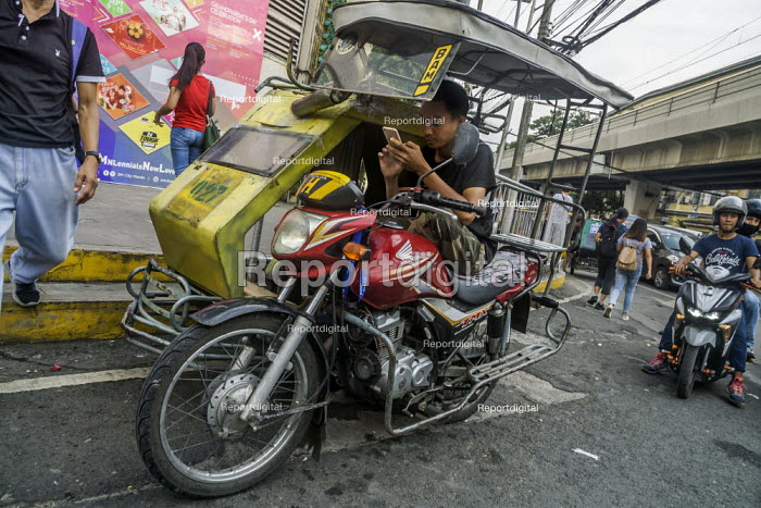 Manila, Philippines: motorcycle taxi driver waiting for a fare - David Bacon - 2019-09-27