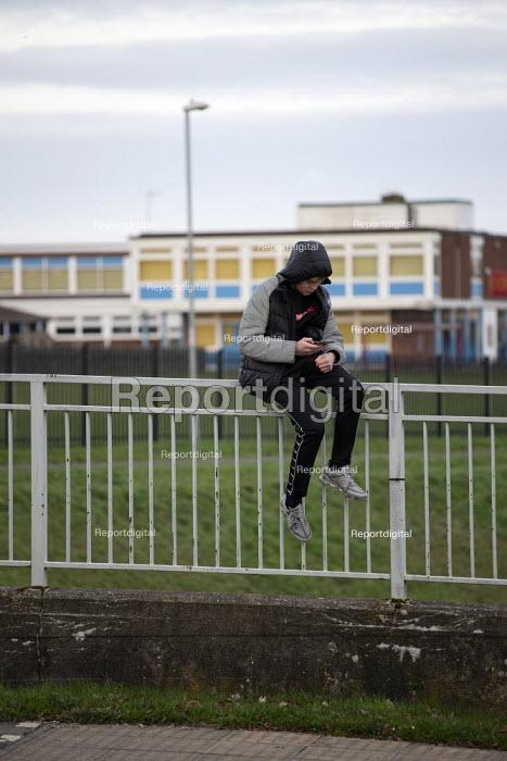 Youth on his mobile phone, Hazel Leys, Corby, Northamptonshire - John Harris - 2019-12-07