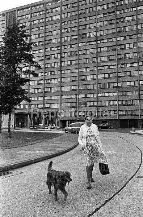 Council house tenant with her dog outside a housing tower block, Newham, East London 1975 - NLA - 1975-06-10