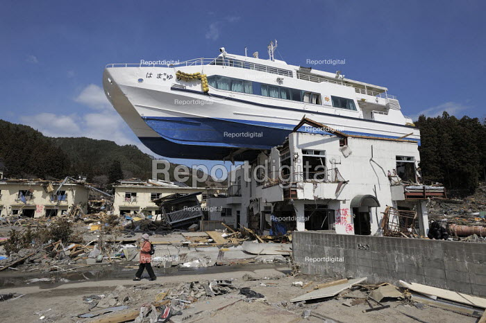 A ship inland on the roof of a building. A survivor returning to seach the devastated Ootsuchi, (Otsuchi) Iwate prefecture, Earthquake and Tsunami, Japan - Kobayashi Masanori - 2011-04-03