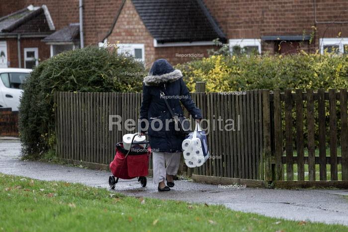 Shopper walking home in the rain, Leamington Spa, Warwickshire - John Harris - 2019-12-12