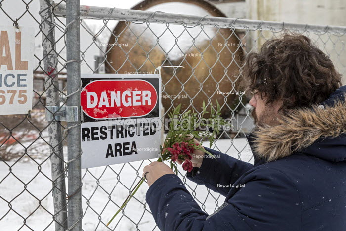 Madison Heights, Michigan USA, Man placing flowers on a fence, Environmental Protection Agency Superfund cleanup site where the owner of Electro-Plating Services dumped toxic chemicals. A green ooze containing hexavalent chromium flowing onto a nearby freeway alerted environmental authorities to the continuing problem - Jim West - 2020-01-19