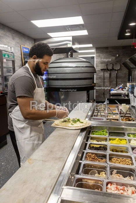 Detroit, Michigan, USA, worker making a pizza, Flamz Pizzeria. The restaurant makes pizzas to order with unlimited toppings, baked in a brick oven - Jim West - 2020-01-25