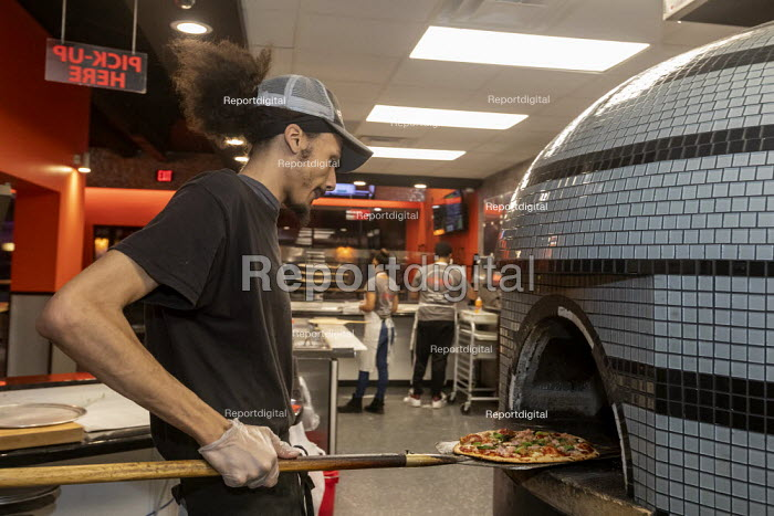 Detroit, Michigan, USA, worker baking a pizza, Flamz Pizzeria. The restaurant makes pizzas to order with unlimited toppings, baked in a brick oven - Jim West - 2020-01-25