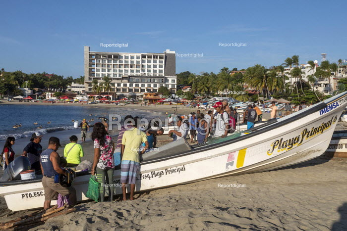 Puerto Escondido beach, Oaxaca, Mexico, customers arriving at dawn to buy fresly caught fish from the crews of small fishing boats - Jim West - 2020-02-04